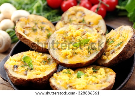 Baked potatoes with cheese and mushrooms on plate close up - stock photo