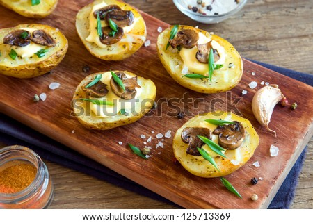 Baked potatoes with mushroom, cheese, greens and sea salt on rustic wooden background - stock photo