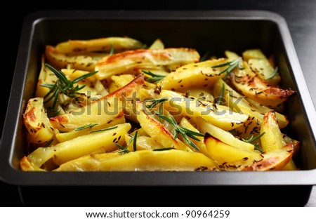 Baked potatoes with rosemary in casserole - stock photo