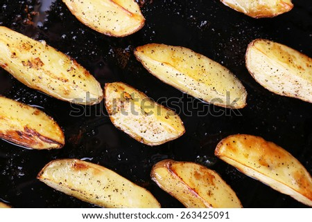 Baked potatoes with spices on pan close up - stock photo