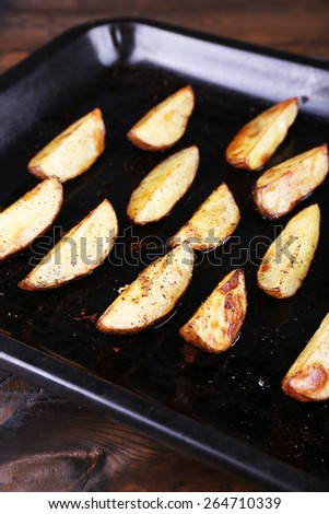 Baked potatoes with spices on pan on table close up - stock photo