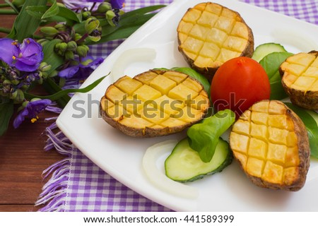 Baked potatoes with vegetables on the background color. Wooden table. Close-up - stock photo