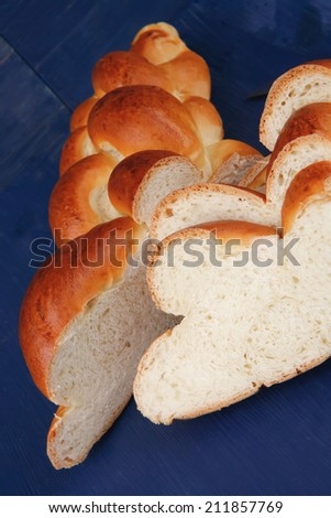 baked product : cuted golden challah on blue wooden table - stock photo