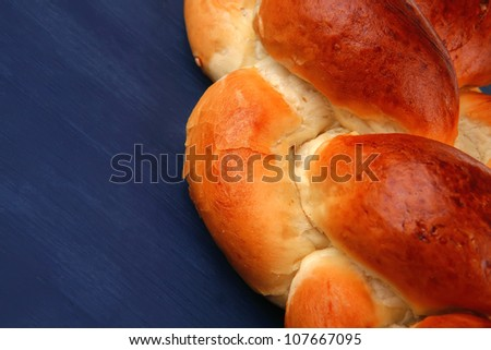 baked product : golden challah on blue wooden table - stock photo