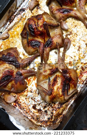 Baked quails and garlic on aluminum foil