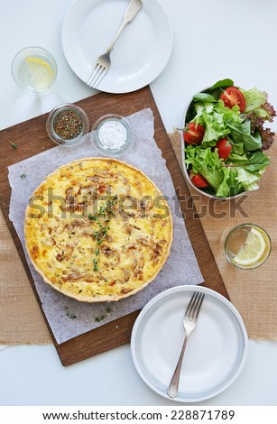 Baked quiche tart frittata with caramelised onions and cheese served with a side green salad - stock photo