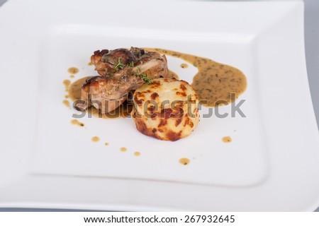 Baked rabbit leg with gravy and mashed potatoes - stock photo