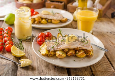 Baked rainbow trout with roasted potatoes and homemade mayonnaise - stock photo
