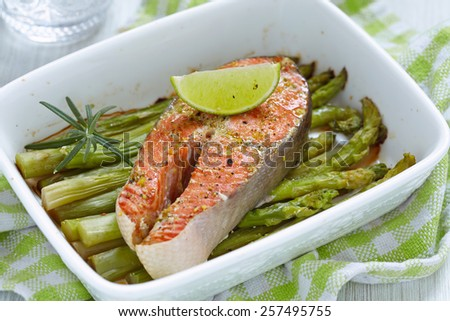 Baked red salmon with asparagus in baking dish - stock photo
