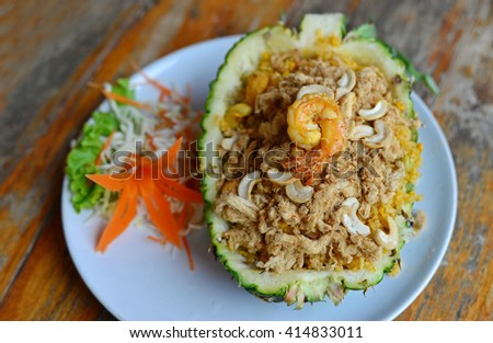 Baked rice with pineapple and shrimp served in a pineapple. (Selective Focus) - stock photo