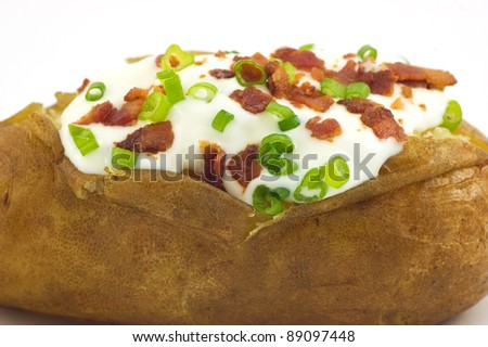 Baked russet potato with sour cream, bacon bits and green onion closeup - stock photo