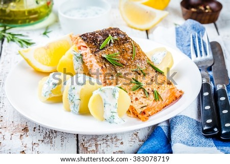 Baked salmon fillet with rosemary and boiled potatoes with dill sauce - stock photo