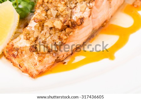 Baked salmon fillet with walnuts and fresh arugula on apricot mousse. Macro. Photo can be used as a whole background. - stock photo
