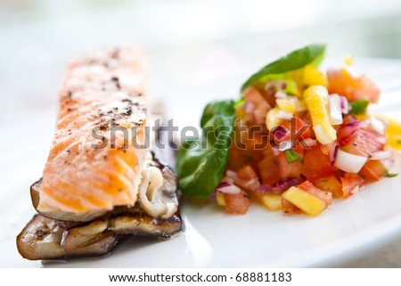 Baked salmon on bed of grill aubergine with serving of mango and tomato salsa - stock photo