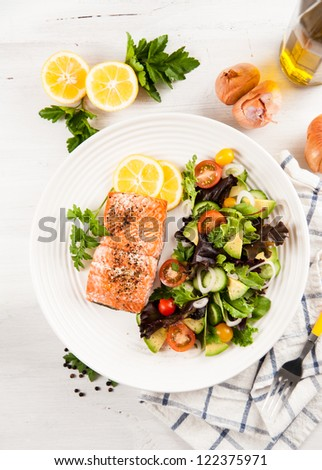 Baked Salmon Served with Tomatoes, Cucumbers, Avocado, Greens Salad