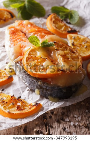baked salmon steak with oranges closeup on baking paper on the table. Vertical