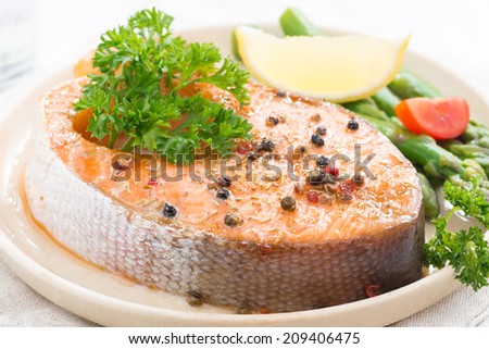 baked salmon with asparagus and lemon on plate, close-up, horizontal