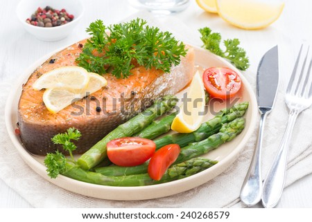 baked salmon with asparagus, parsley and lemon on plate, close-up