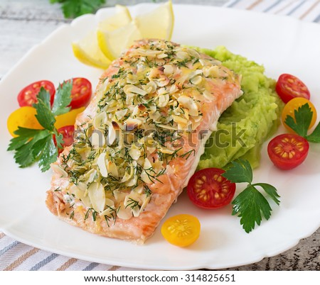 Baked salmon with cheese and almond crust and garnished with mashed potatoes and green peas - stock photo