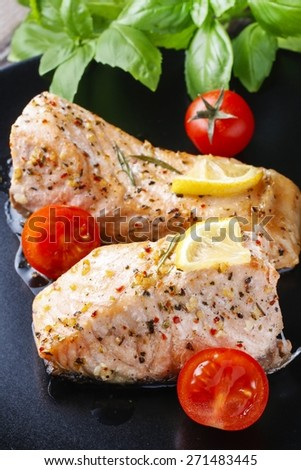 Baked salmon with herbs on the black plate - stock photo