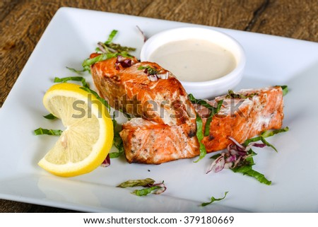 Baked salmon with sauce served lemon