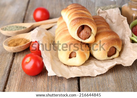 Baked sausage rolls on wooden table close-up - stock photo