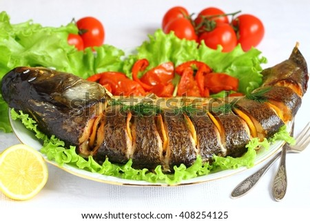 baked silver carp  with tomato and lemon - stock photo