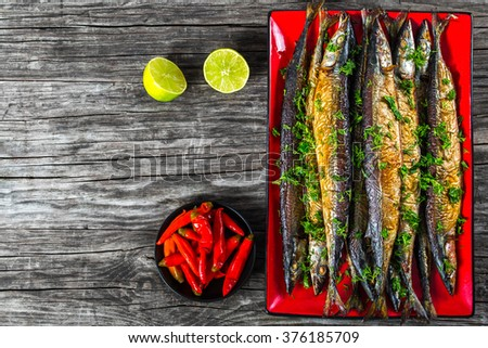 Baked spiced saury decorated with dill on a red rectangular dish on an old wooden table with pickled chili pepper on a small plate and a liemon, close-up top view - stock photo