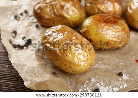 Baked spicy potatoes on parchment, closeup - stock photo
