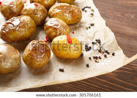 Baked spicy potatoes on parchment on wooden table, closeup - stock photo