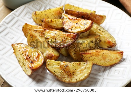 Baked spicy potatoes on white plate, closeup - stock photo