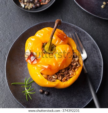 Baked stuffed bell peppers filled with spelt wheat, rice, vegetables on a dark plate stone background Top view - stock photo