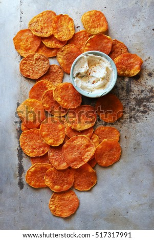 Baked sweet potato chips with yogurt dip on a tray.Top view