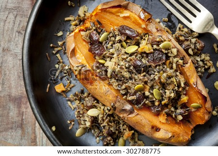 Baked sweet potato or yam, stuffed with wild rice, pepitas, and cranberries. - stock photo