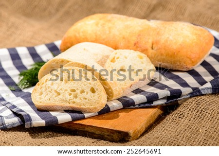 Baked to perfection. Closeup shot of a sliced home-baked bread ciabatta and fennel on a wooden board with a farm style checkered napkin - stock photo