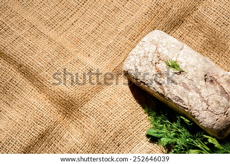 Baked to perfection. Top view of a fresh home baked loaf of bread and green fennel on a farm style sackcloth with copy space - stock photo