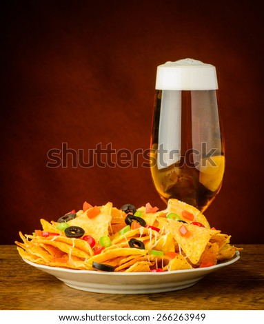 baked tortilla chips with cheese, olives and chili peppers and glass of beer - stock photo