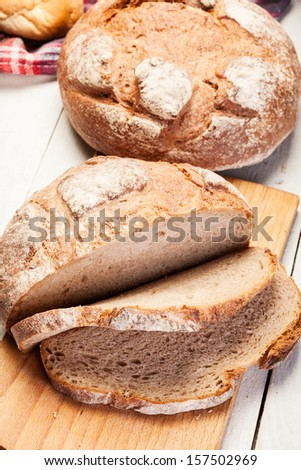Baked traditional bread on wooden table  - stock photo