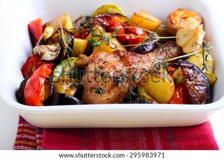 Baked vegetables and chicken drumstick in baking tin - stock photo