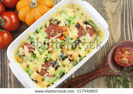 Baked vegetables with cheese in the pot on the table