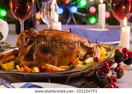 Baked whole chicken for Christmas dinner on festive table - stock photo