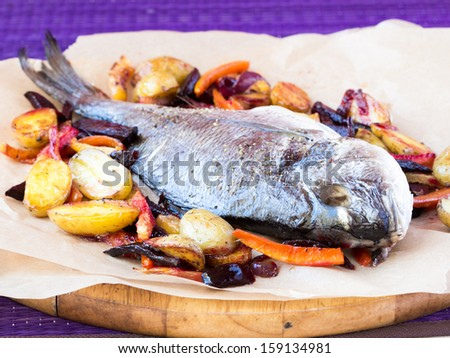 Baked whole fish dorada with grilled stew of roots - stock photo