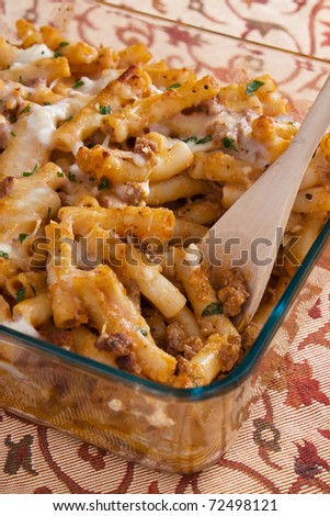 Baked ziti pasta with meat, tomato sauce, mozzarella, parmesan, and ricotta cheese. - stock photo