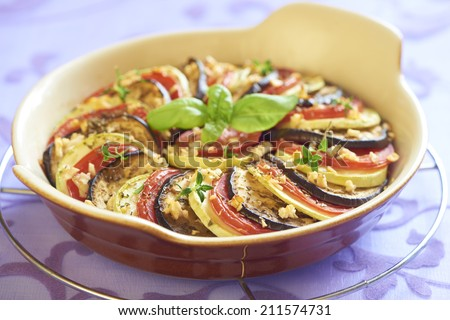 Baked zucchini, tomatoes and eggplant with garlic and herbs - stock photo