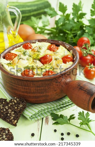 Baked zucchini with chicken, cherry tomatoes and herbs in a ceramic pot