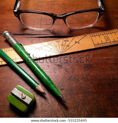 Bakelite pencil sharpener, vintage green pencils, ruler, and retro spectacles on antique wood desktop.