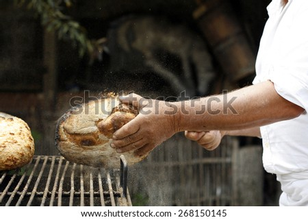 Baker from Transylvania preparing special bread, removing crust, process - stock photo