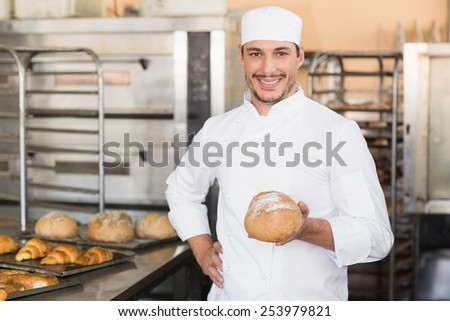 Baker holding a freshly baked loaf in the kitchen of the bakery - stock photo