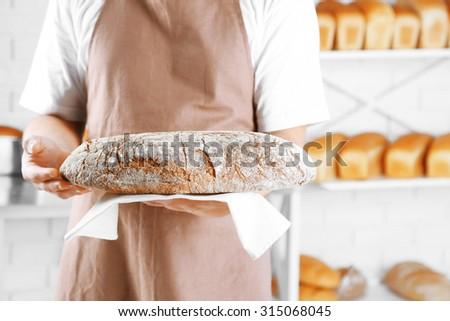 Baker holding freshly baked bread in kitchen of bakery - stock photo