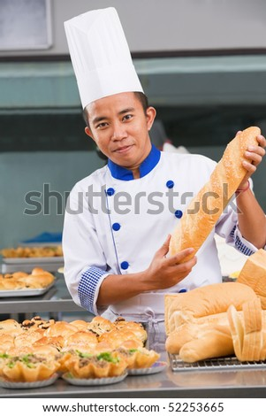 Baker holding the bread in commercial kitchen - stock photo